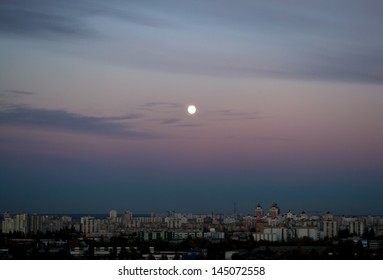 Evening cloudscape with moon in city