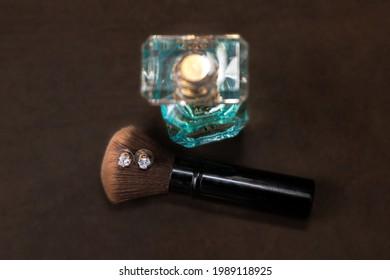 Evening clutch bag, makeup brush, earrings and perfume closeup