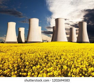 Evening colored sunset view of Nuclear power plant Jaslovske Bohunice with golden flowering field of rapeseed - Slovakia - two possibility for production of electric energy