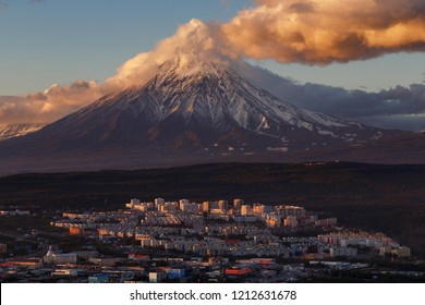 Evening colorful top view of townscape of Petropavlovsk-Kamchatsky City at sunset on background clouds drifting across blue sky, cone of active Koryak Volcano. Kamchatka Peninsula, Russian Far East.