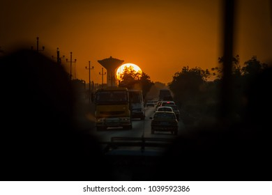 Evening commute on african roads in Senegal. View from a bus towards the sunset and a water tower on a busy african road.