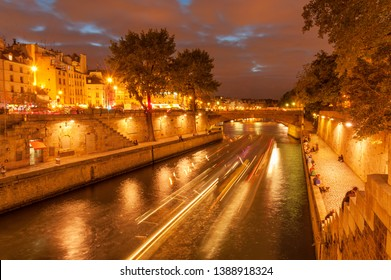 Evening cruise on Seine river in slow motion and people hanging out along embankment of Ile de la Cite at night time in Paris downtown, France