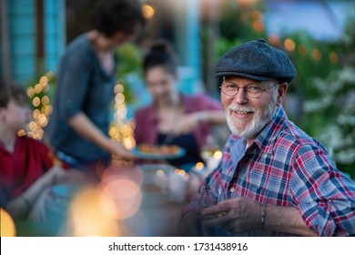 in the evening, dinner with family around a table in the garden, in front of the wooden house. A friendly bearded dad is looking at camera