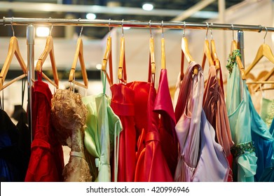 Evening dresses hang on a shelf in store