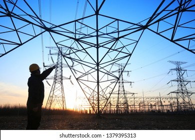 In the evening, electricity workers and pylon silhouette