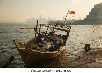 Evening embankment in Manama Bahrain, fishing traditional wooden boat with flag, sunset, urban landscape.
