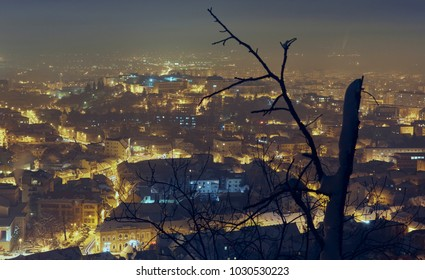 Evening fall and city lights in snow covered Brasov city, Romania. Twilight winter cityscape with leafless tree branches. Bird's eye view.