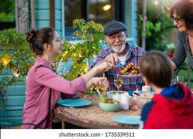 Am Abend ein Familienessen im Garten. Jeder hilft sich glücklich, das Gericht der Mutter zu bedienen.
