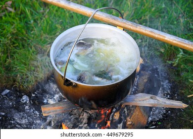 Evening fish soup a bowler hat over a campfire after a successful fishing