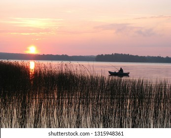 Evening fishing. Silhouette of a fisherman in a boat on the big lake. Fishing against the setting sun. Sedge growing along the shore.
