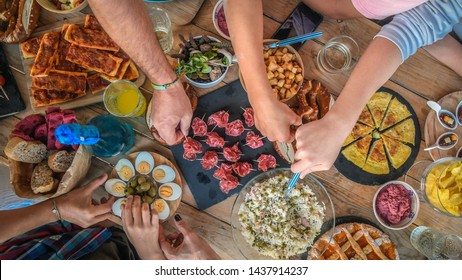 Evening with friend dinner on the terrace enjoying together. Summer aperitif with group of friends Joy and festivities in family View from the top of a table with many foods Happy hands taking viands