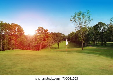 The evening golf course has sunlight shining down at golf course in Thailand