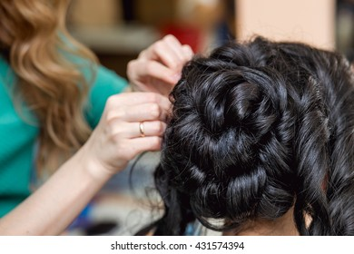 evening hairstyle. brunette doing hairdresser and styling in barber salon