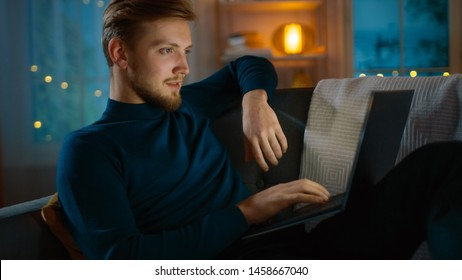 In the Evening Handsome Young Man Relaxes at Home Laying on a Couch in the Living Room Works on a Laptop Computer, Looks at Infographics and Statistics.