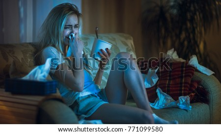 In the Evening Heartbroken Girl Sitting on a Sofa, Crying, Using Tissues, Eating Ice Cream and Watching Drama on TV. Her Room is in Mess.