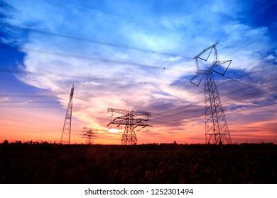 In the evening, high voltage towers silhouette and a beautiful sunset