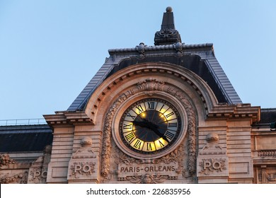 Evening illumination of famous ancient clock on the wall of Orsay Museum in Paris