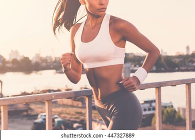 Evening jog. Close-up of beautiful young woman in sports clothing running along the bridge and looking over shoulder