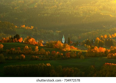 Evening in Kasperske hory with church, Sumava, Czech Republic. Cold day in Sumava National park, hills and villages in orange trees, misty view on czech landscape, autumn scene.