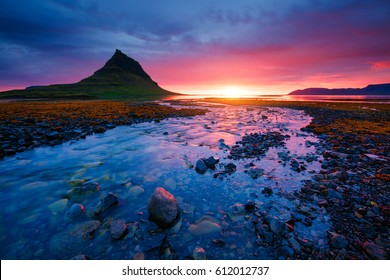 Evening Kirkjufell volcano the coast of Snaefellsnes peninsula. Location Kirkjufellsfoss sightseeing Europe. Typical Icelandic landscape. Breathtaking picture of wildlife. Explore the world's beauty.