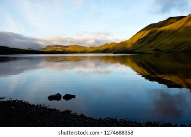 Evening Langisjór. The lake captured from the southwest bank with mountain rig Fögrufjöll behind the water. The mountains partially reflects in the slightly waved water that is already in the shadow.