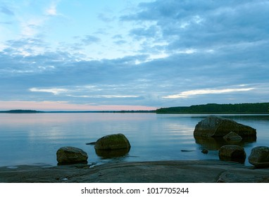 Evening landscape. Lake after sunset, pink and blue sky and reflection in the water. Stone shore and rocks in the water. Russia, Finland, Karelian Isthmus, Lake Vuoksa