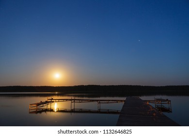 Evening landscape of moon rise over calm lake