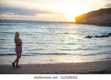 evening landscape. pretty woman is walking along  seashore