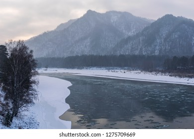 Evening landscape of the river in a mountainous area with ice floes in the winter season