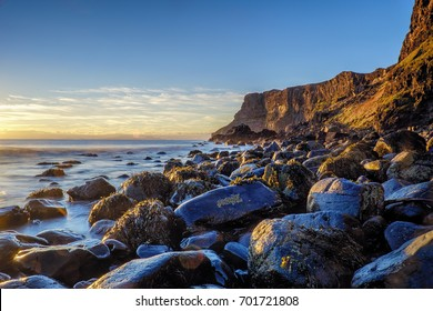 Evening light on the rocks, boulders and cliff face of Talisker Bay, Isle of Skye