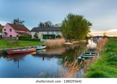 Evening light over boats moored by pretty cottages at West Somerton on the Norfolk Broads