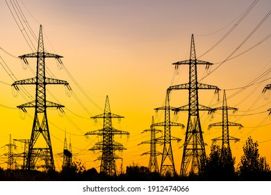Evening light. Sunset casting red and orange light. Silhouettes of the electric power masts and cables, pylons. Electricity power station.
