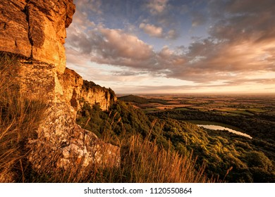 Evening light from Sutton Bank, Englands finest view. Lake Gormire and the Vale of York bathe in golden sunlight in the distance.