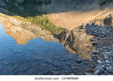 Evening mirrow of rock cliffs at Moraine Lake in clear mountain lake water. Alberta Canada