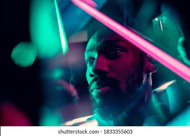 Evening mood. Cinematic portrait of stylish young man in neon lighted room. Bright neoned colors. African-american model, musician indoors. Youth culture in party, festival style and music concept.