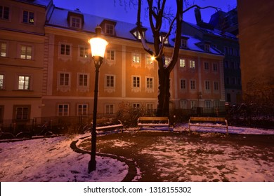 Evening mood at deserted park with snow left lit by a street lamp at Spittelberg in Vienna between historic houses of the old town in Advent.