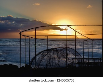 Evening mood in front of the Atlantic. In the foreground are large fishpots of the fishermen, they form a black contrast to the golden yellow sky, the Atlantic Ocean is calm evening sky