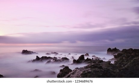 Evening mood on the Atlantic Ocean in gentle purple tones in HD recording. The water is gentle and misty, very soft and mellow with the sky. Out of the water, black volcanic rocks.