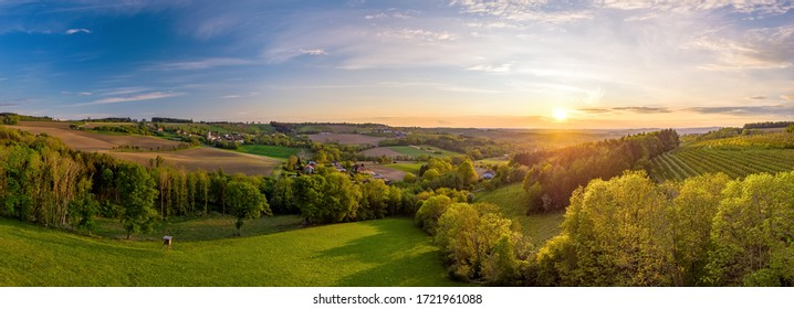 Evening mood over an Upper Austrian cultural landscape in spring with trees and fields in the foreground