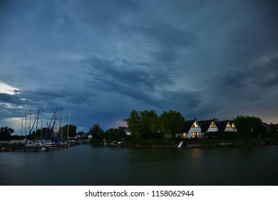 Evening mood with storm cloud and lightning strike in background over cottage settlement Seepark Weiden at Lake Neusiedlersee in Austria. Sunset light rays are reflected in windows of holiday homes.