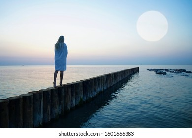evening or Morning walk of pretty blond woman. caucasian blonde girl walking on sunset beach. log direct way to horizon . rear, back view. white wet towel on shoulders. moon light above water.
