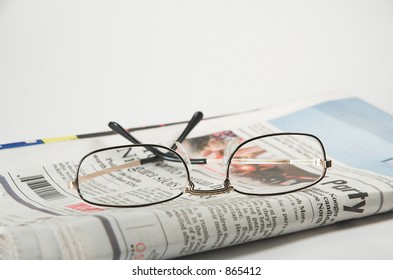 Evening newspaper with reading glasses