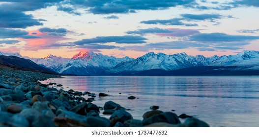 An Evening On Lake Pukaki With Mt Cook, Aoraki, In New Zealand. The Setting Sun Paints The Southern Alps With Light