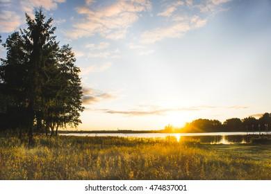 Evening orange sunset over Valday lake, Russia nature landscape photography. Autumn sunset, outdoor nature of Russia. Fantastic sunset over lake near green meadow. Autumn nature sunset, Russia.