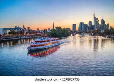 Evening over Main river with touristic cruise boat, illuminated embankment and Frankfurt skyline of modern architecture at sunset, Germany, Europe