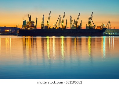 Evening panorama of the cargo port. Loading and unloading of ships. Crane