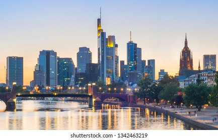Evening panorama of illuminated Frankfurt downtown with modern architecture at Main river bank, Germany, Europe