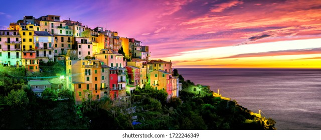 Evening panorama of the medieval town of Cornilla in the Cinque Terre National Park in November, purple sunset and colorful houses in Liguria