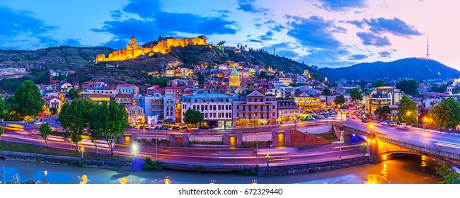 The evening panorama of the old town, located on Sololaki hill, crowned with brightly illuminated Narikala fortress, the Kura river reflects the evening city lights, Tbilisi, Georgia.