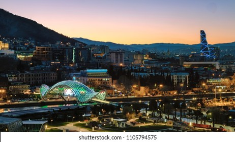 Evening panorama of Tbilisi with city lights and view to The Bridge of Peace